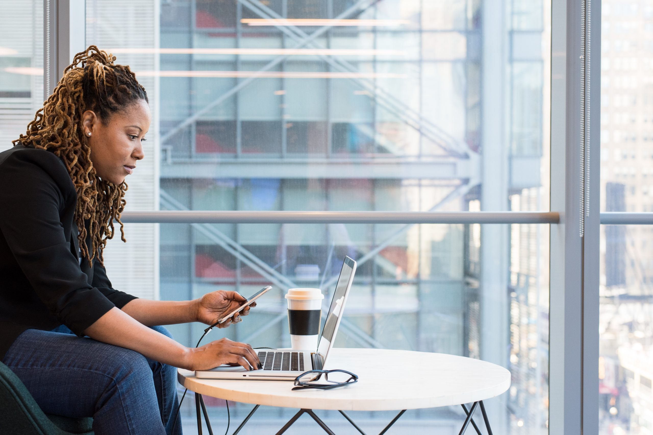 woman of color on computer and phone