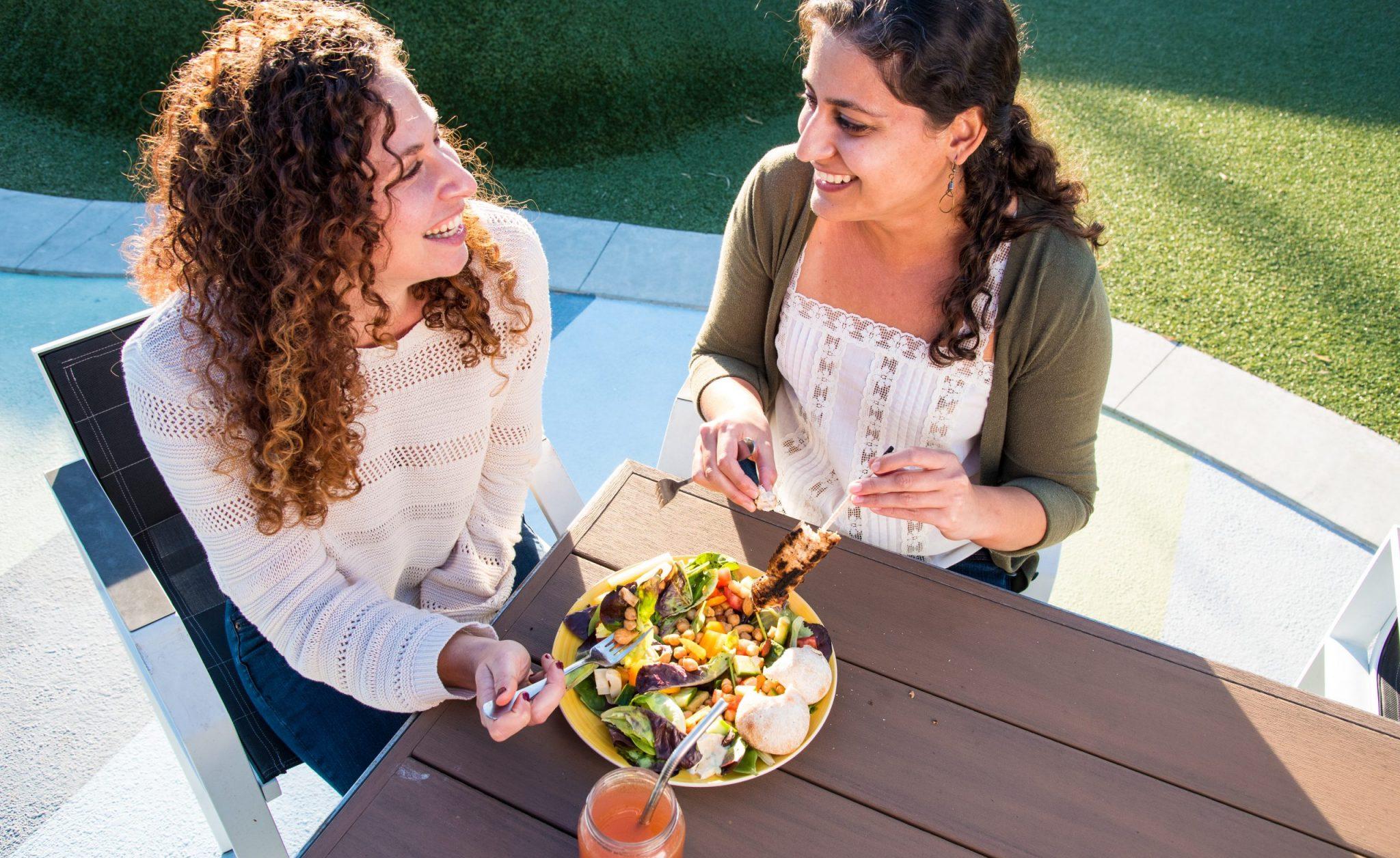 two women eating salad, smiling